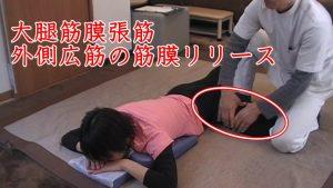 股関節外転外旋位にて筋膜はがし。カエルの足のように膝を腰まで上げて、大腿の外側の筋肉をほぐす。大腿筋膜張筋は膝下まで続く腸脛靭帯に繋がり、ここの部分は足を伸ばして押さえると痛いので、この姿勢で筋膜をつまむように伸ばしていきます。ランニングなどで疲労してくると硬くなって突っ張りやすくバネ股といわれる股関節でばねがはじかれるような症状が出ます。座骨神経痛よりもバネ股がつらい場合は、ここの筋膜リリースをしながら足を上げたり伸ばしたり動作をしながらの筋膜を伸ばしていきます。