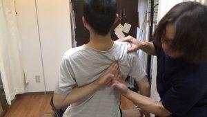 肩甲骨はがしで自分の肩甲骨に指を入れる